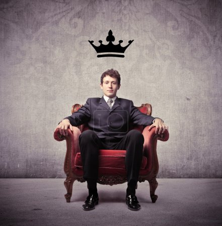 Businessman sitting on an armchair with a crown ov...