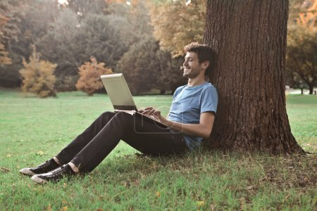 Photo for Young man sitting under a tree in a park and using a laptop - Royalty Free Image