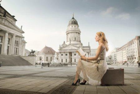Foto de Hermosa mujer sentada en una maleta y leyendo un libro con el Museo en el fondo - Imagen libre de derechos