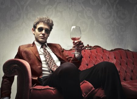 Photo for Elegant young man sitting on a velvet sofa and holding a glass of wine - Royalty Free Image