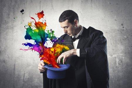 Photo pour Jeune magicien extrayant des ondes colorées de son chapeau de cylindre - image libre de droit