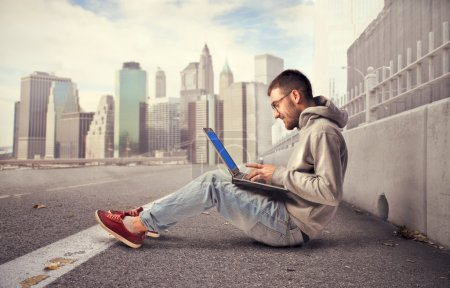 Photo for Young man using a laptop on a city street - Royalty Free Image