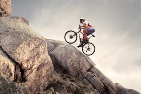Photo for Cyclist riding a mountain bike on some rocks - Royalty Free Image