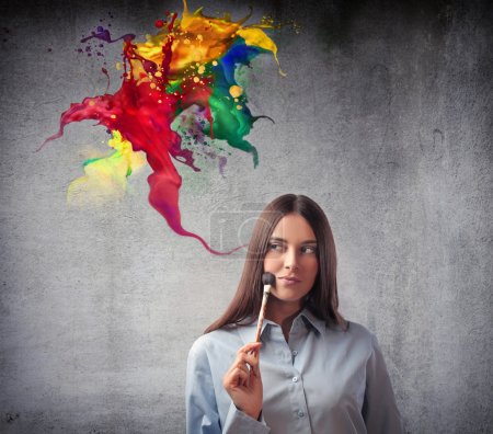 Photo for Beautiful woman holding a paintbrush and colors coming out of her head - Royalty Free Image