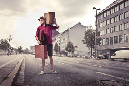 Photo pour Jeune homme portant de nombreuses valises dans une rue de la ville - image libre de droit