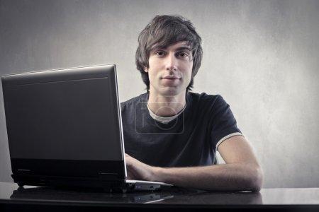 Photo pour Jeune homme utilisant un ordinateur portable - image libre de droit
