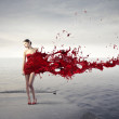 Beautiful woman with her dress melting in red pain...