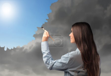 Photo for Beautiful woman painting a sunny sky over a cloudy one - Royalty Free Image
