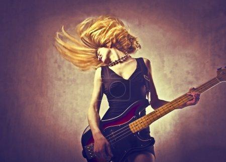 Photo pour Jeune femme headbanging tout en jouant de la guitare basse - image libre de droit