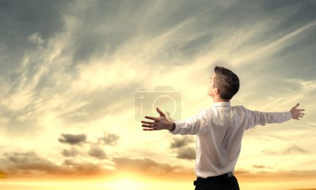 Photo for Young businessman stretching out his arms to the sun - Royalty Free Image