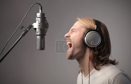Photo for Young man singing out loud into the microphone of a recording studio - Royalty Free Image