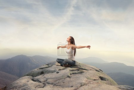 Photo for Beautiful woman sitting on a peak in the mountains and stretching out her arms - Royalty Free Image