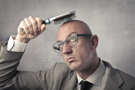 Bald businessman try to brush his head
