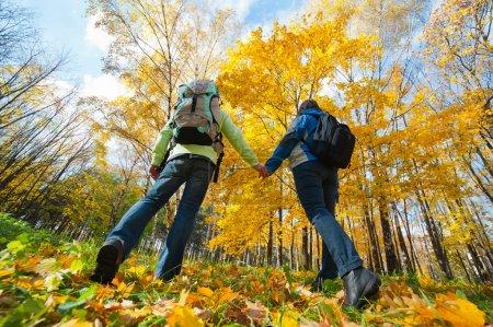 Photo pour Jeune couple avec des sacs à dos dans le parc. Chute . - image libre de droit
