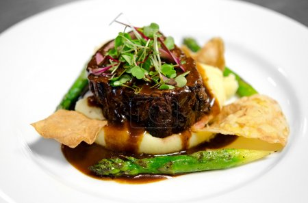 Photo for Image of a steak filet on a bed of mashed potatoes with asparagus, chips and gravy - Royalty Free Image