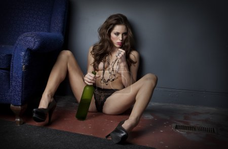 Photo for Attractive nearly-naked woman seated on grungy floor holding half empty bottle of wine between her legs. - Royalty Free Image