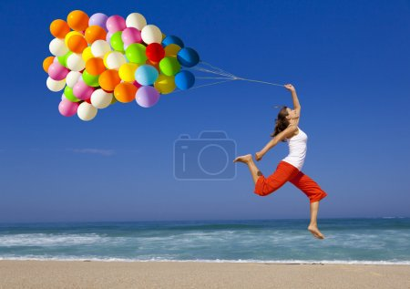 Photo for Beautiful and athletic Girl jumping with a balloon on the beach - Royalty Free Image