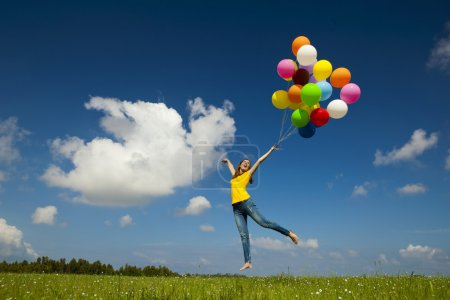 Photo for Happy young woman holding colorful balloons and flying over a green meadow - Royalty Free Image