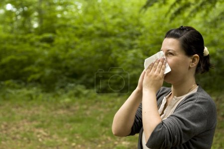 Photo for Brunette woman having a pollen allergy in the forest - Royalty Free Image
