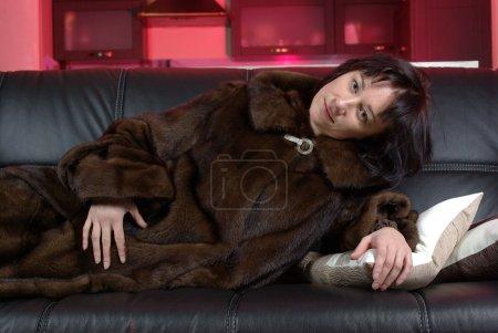Photo pour Allongé féminin dans un manteau de vison sur le canapé - image libre de droit