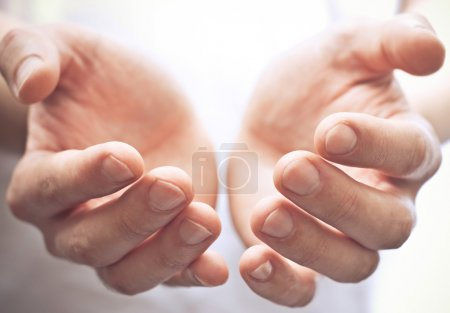Male hands as if holding something. Focus on finge...