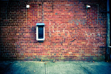 A grungy urban brick wall with an obsolete, out of...