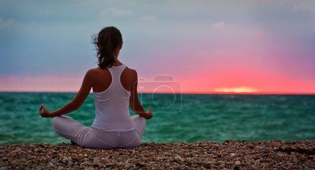 Photo pour Jeune brune assise en position lotus sur la plage. Espace de copie - image libre de droit