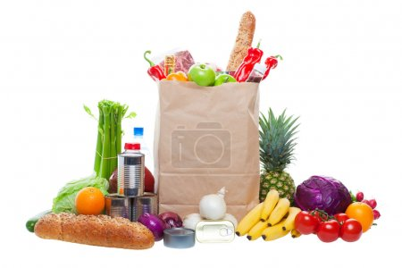 Photo for A paper bag full of groceries, surrounded by fruits, vegetables, bread, bottled beverages, and canned goods. Studio isolated on White background - Royalty Free Image