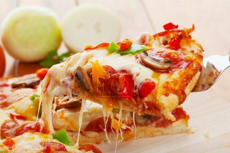 Photo for A Slice of supreme pizza being lifted up - Royalty Free Image