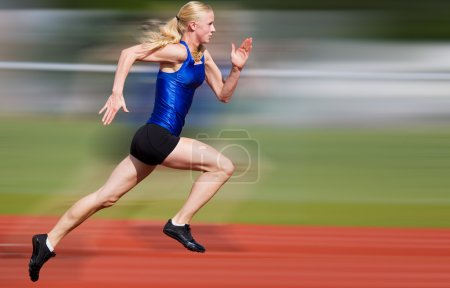 Photo for Young athlete running down the track with motion blur added - Royalty Free Image