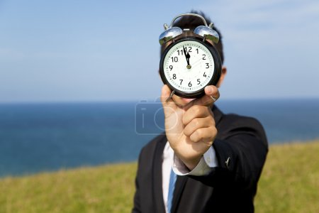 Photo for Businessman holding clock and standing on the field - Royalty Free Image