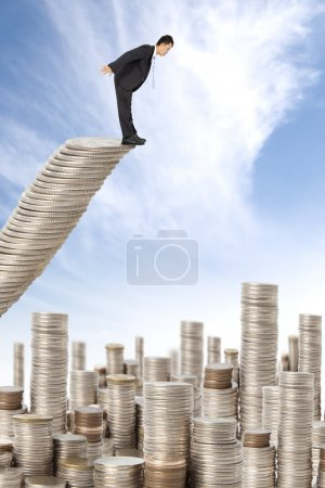 Surprised businessman standing on the money stairs and watching many coin t