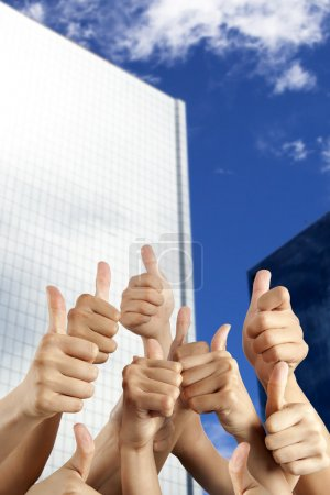 s hand with thumbs up in front of modern building