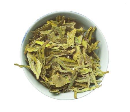 Photo pour Bol avec thé vert sec en vrac, longue variété de feuilles, isolé sur blanc, vue sur le dessus - image libre de droit