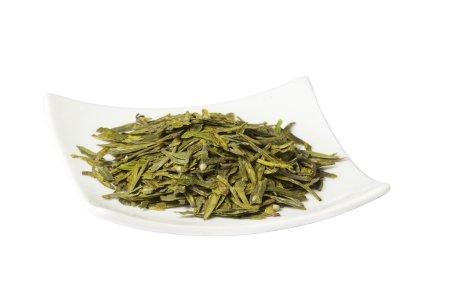 Photo pour Assiette avec thé vert sec en vrac, longue variété de feuilles, isolée sur blanc - image libre de droit