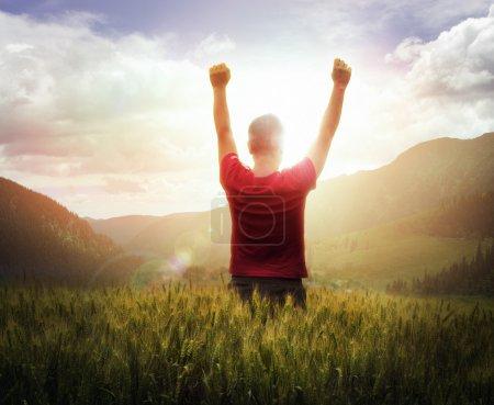 Photo pour Jeune homme, les bras levés en pensant au coucher du soleil avec des montagnes - image libre de droit