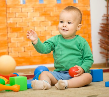 Photo for Little boy is playing with toys in preschool while sitting on floor - Royalty Free Image