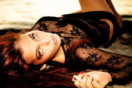 Photo pour Femme de beaux cheveux rouge au coucher du soleil sur la plage avec la cigarette - image libre de droit