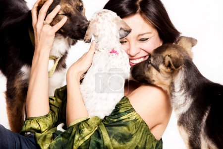 Happy woman with three adopted street dogs, studio shot