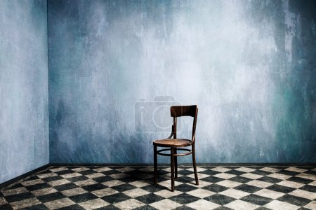 Photo for Room with old blue walls and tiled floor with wooden chair in the middle - Royalty Free Image