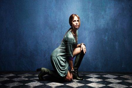 Photo pour Belle femme posant sur le sol, plan complet du corps, plan intérieur - image libre de droit