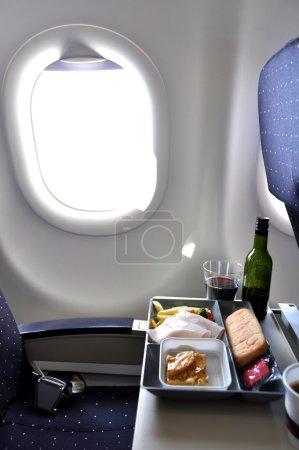 Photo pour Plateau déjeuner et bouteille de vin dans un avion - image libre de droit