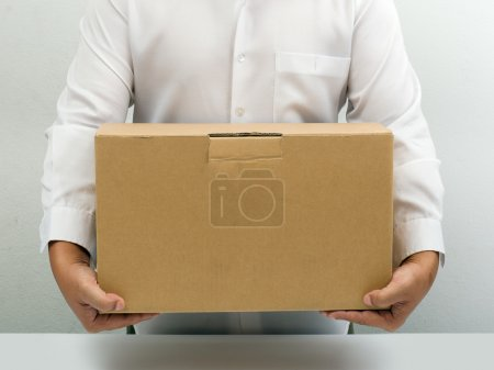 Man in white shirt carry brown paper box hand unde...