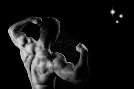 Photo for Young sports guy with a naked torso on a black background - Royalty Free Image