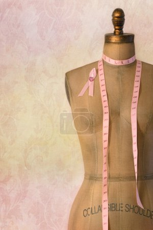 Pink breast cancer ribbon on mannequin with vintage background