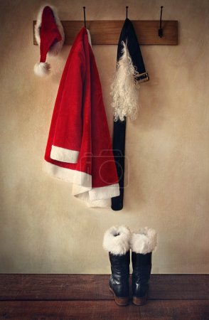 Photo for Santa costume with boots on coat hook - Royalty Free Image