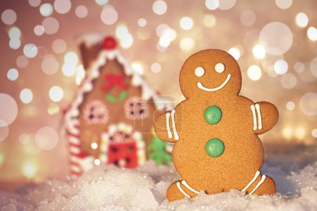 Gingerbread man cookie standing beside house