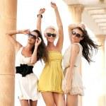Three cheerful women wearing sunglasses...