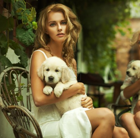 Portrait of a young blonde hugging a cute puppy