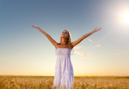 Photo pour Belle femme marchant sur le champ de blé avant le coucher du soleil - image libre de droit